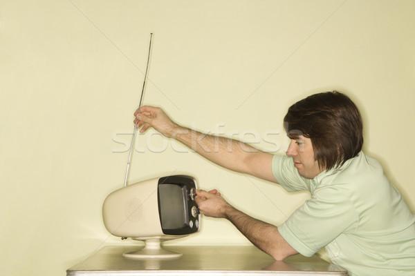 Adam ayar televizyon yandan görünüş kafkas oturma Stok fotoğraf © iofoto