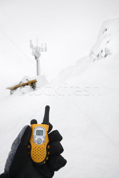 Gloved hand holding walkie talkie. Stock photo © iofoto