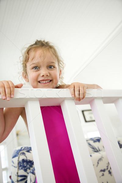 Girl peeking over railing. Stock photo © iofoto