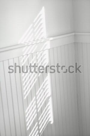 Stock photo: Sun through window blinds on wall.