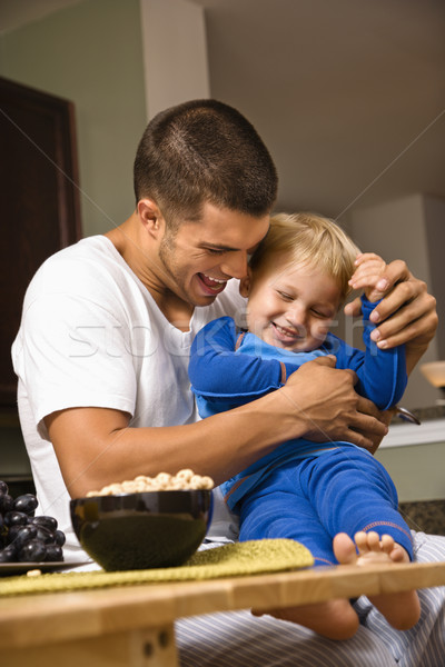 Stock photo: Dad tickling son.