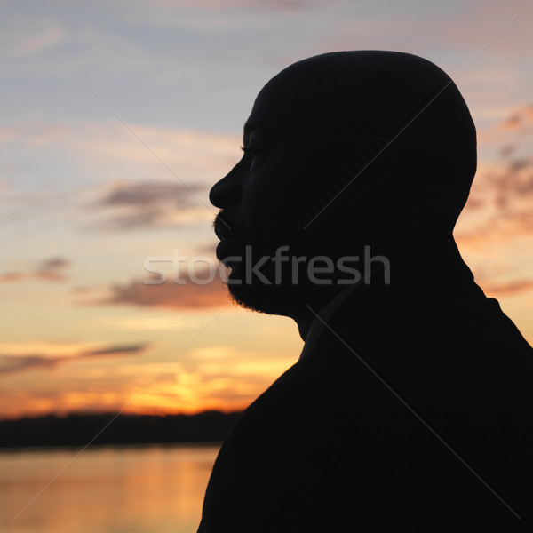 African-American man standing by water at sunset in Washington, DC, USA. Stock photo © iofoto
