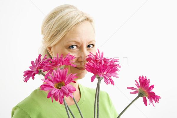 Kobieta patrząc kwiaty portret uśmiechnięty dorosły Zdjęcia stock © iofoto