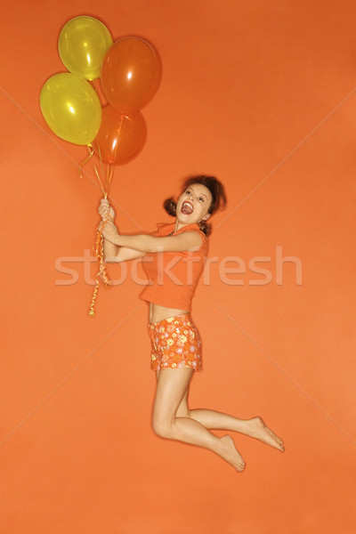 Woman lifted by balloons. Stock photo © iofoto