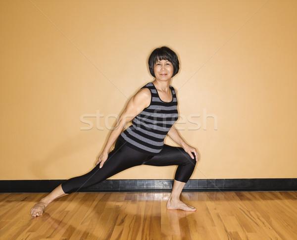 Woman Stretches Leg in Yoga Pose Stock photo © iofoto