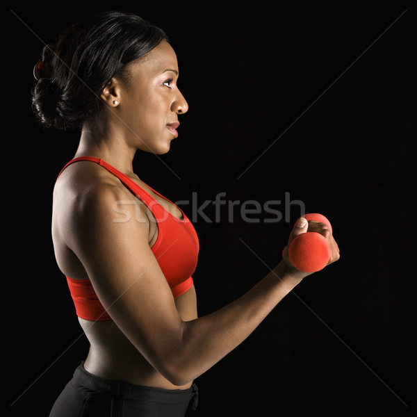 Woman lifting dumbbell. Stock photo © iofoto