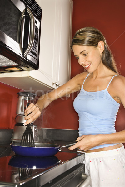 Attractive Young Woman in Kitchen Cooking Stock photo © iofoto