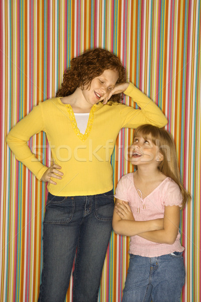 Girl leaning on smaller girl. Stock photo © iofoto