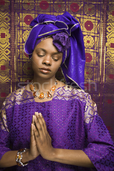 Young African American Woman Praying and Wearing Traditional African Dress Stock photo © iofoto