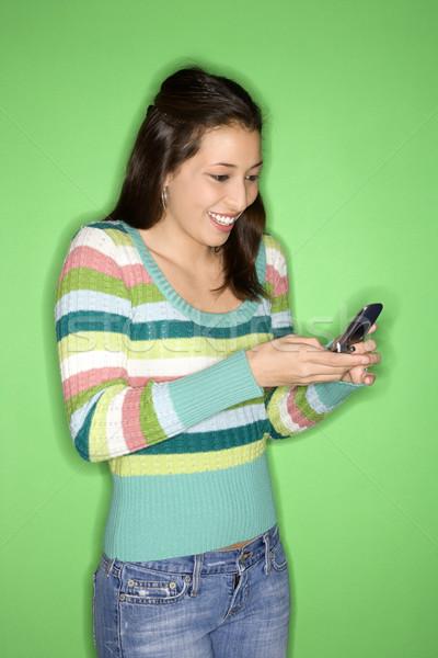Teenage girl using cellphone. Stock photo © iofoto