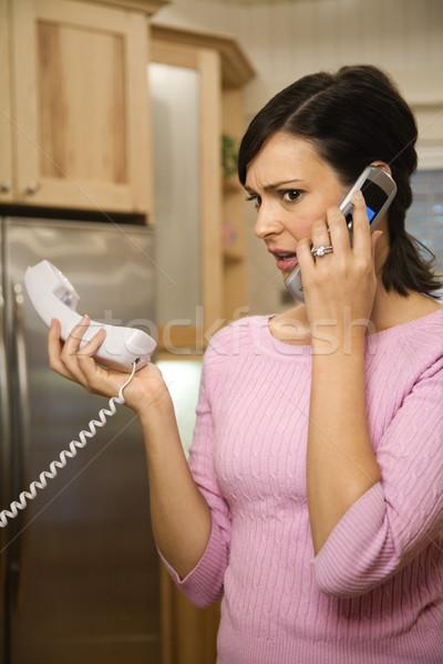 Serious woman on two telephones. Stock photo © iofoto