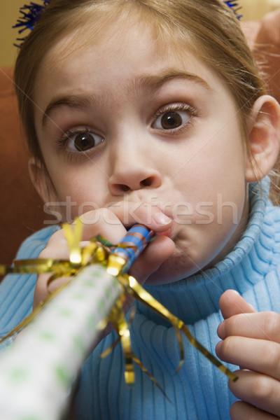 Girl blowing noisemaker. Stock photo © iofoto