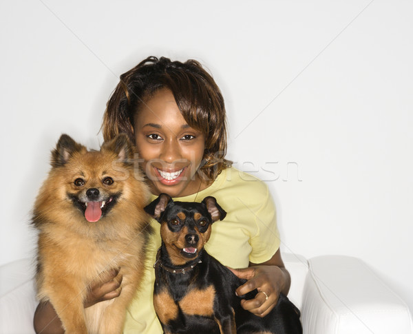 Stock photo: Woman holding dogs.