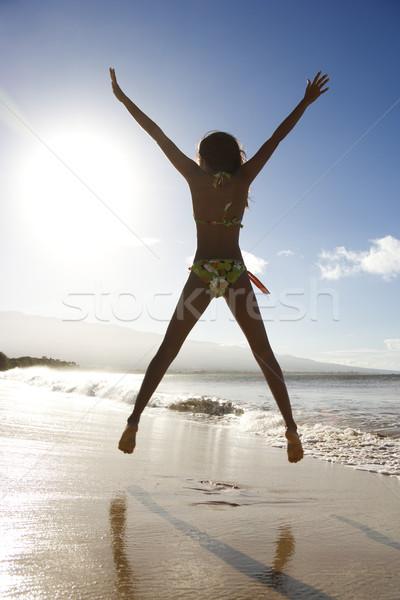Girl jumping on beach. Stock photo © iofoto
