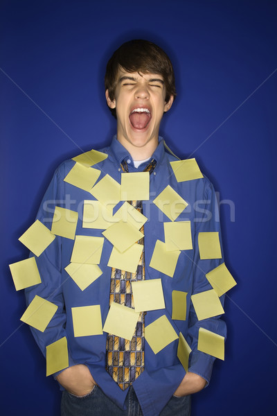 Caucasian teen boy covered with sticky notes screaming. Stock photo © iofoto