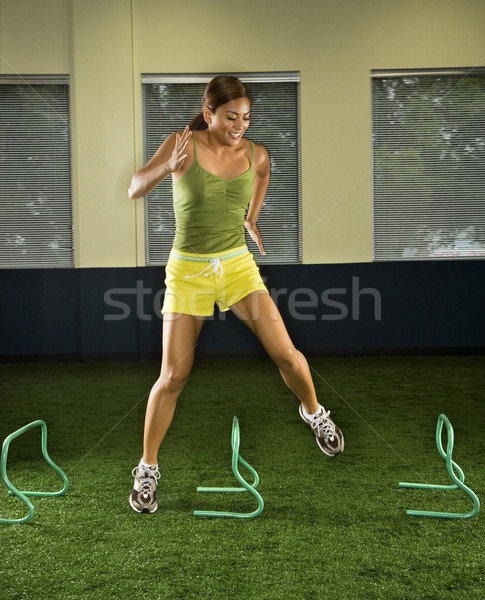 Woman jumping hurdles. Stock photo © iofoto