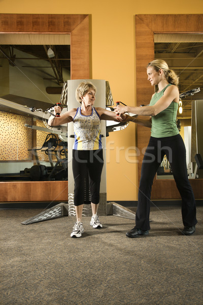 Woman helping woman excercise. Stock photo © iofoto