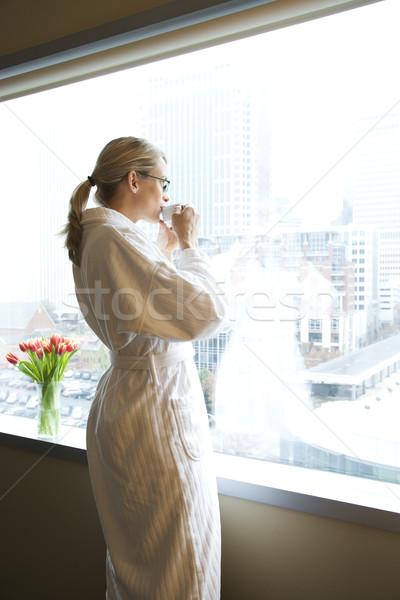 Kobieta pitnej kawy filiżankę kawy patrząc Zdjęcia stock © iofoto