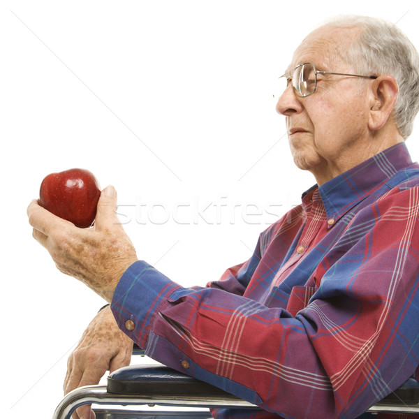 Elderly man holding apple. Stock photo © iofoto