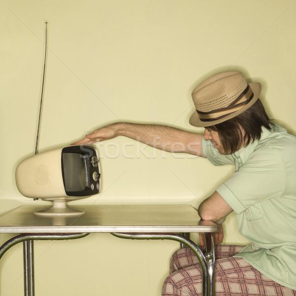 Man tapping retro TV. Stock photo © iofoto