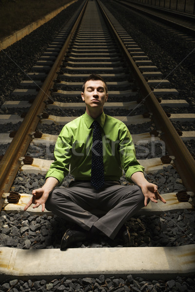 Businessman Meditating on Railroad Tracks. Stock photo © iofoto