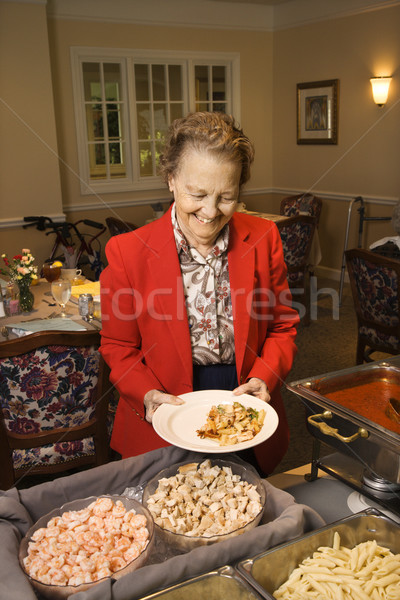 Vrouw buffet voedsel ouderen kaukasisch eetkamer Stockfoto © iofoto