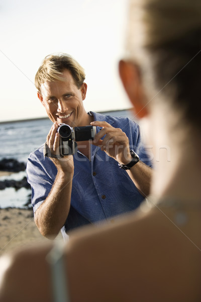 Stock photo: Smiling Man Filming Woman At Beach