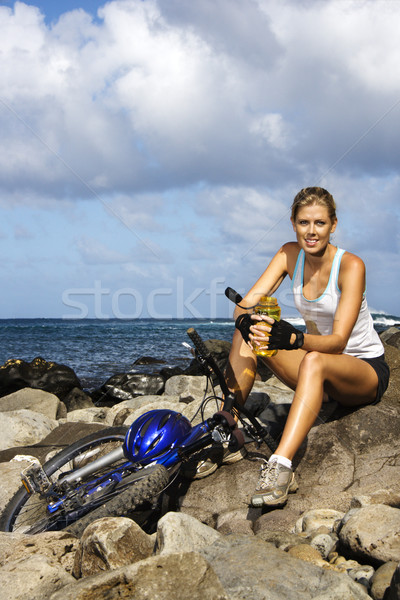 Attractive Young Woman Sitting With Bicycle on Rocky Coast Stock photo © iofoto