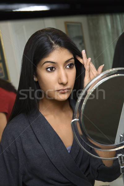 Young woman looking in mirror. Stock photo © iofoto