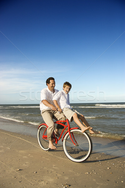 Dad riding red bicycle with son on handlebars.  Stock photo © iofoto