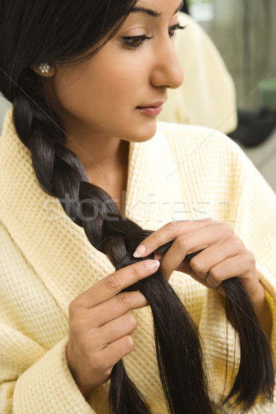 Young woman braiding hair. Stock photo © iofoto