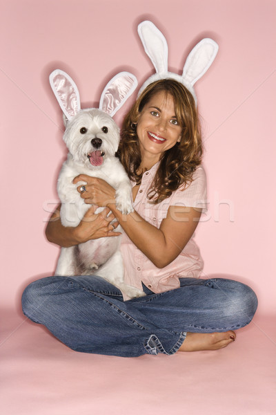 Woman and dog wearing rabbit ears. Stock photo © iofoto