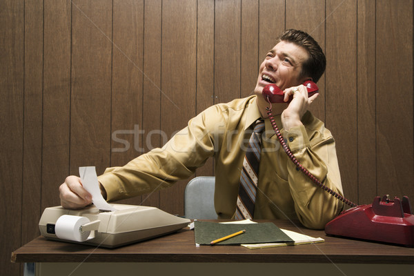 Businessman punching numbers. Stock photo © iofoto