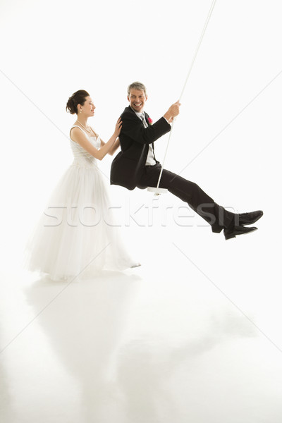 Bride pushing groom in swing. Stock photo © iofoto