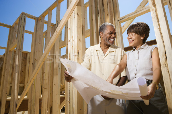 Couple Holding Building Plans on Construction Site Stock photo © iofoto