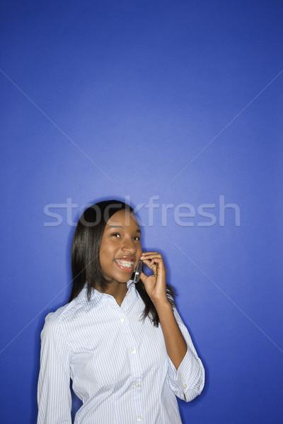 Girl smiling on cellphone. Stock photo © iofoto