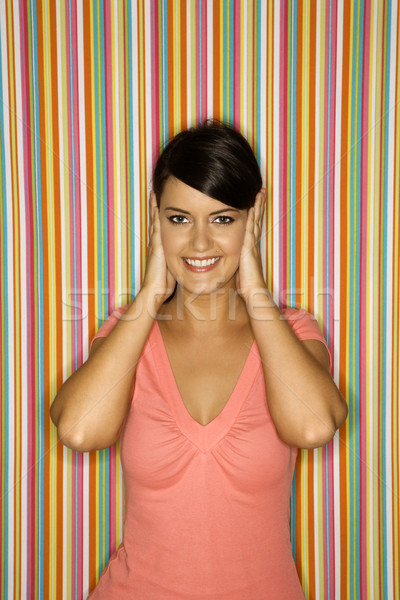 Stock photo: Smiling woman covering ears.