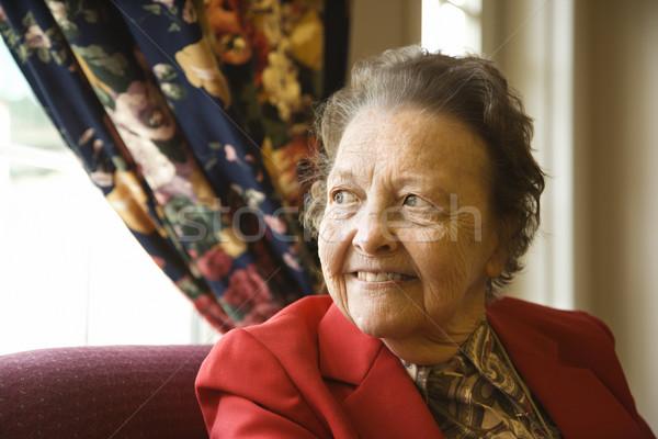 Elderly woman by window. Stock photo © iofoto