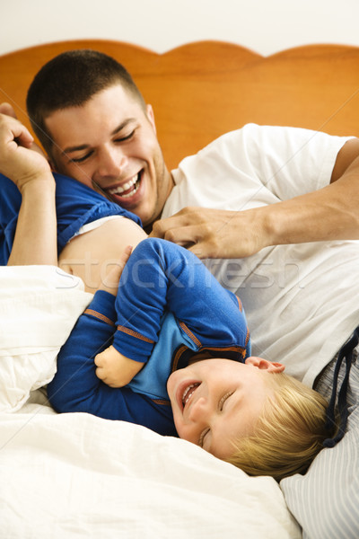 Stock photo: Dad tickling child.