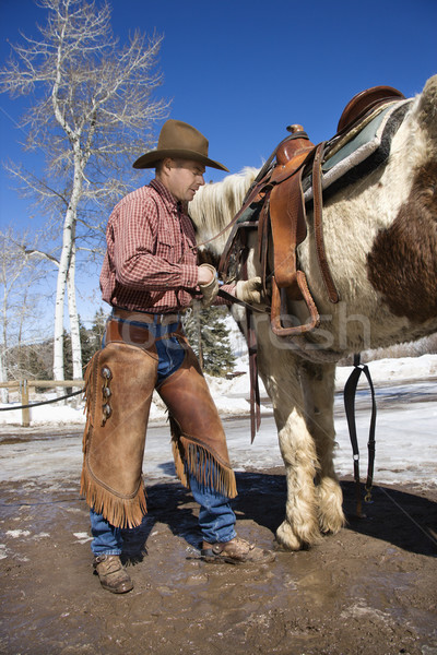 Kovboy eyer at adam ayakta yukarı Stok fotoğraf © iofoto