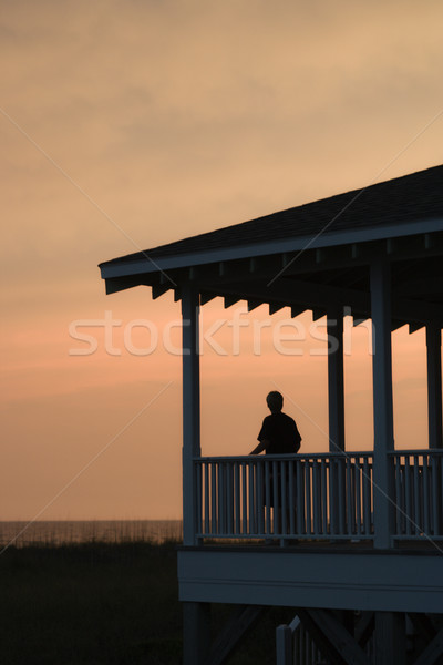 Boy on beachfront porch at sunset Stock photo © iofoto