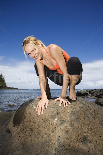Woman squatting on large rock. Stock photo © iofoto