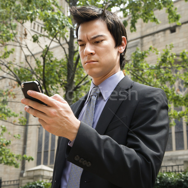 Businessman looking at cell phone. Stock photo © iofoto
