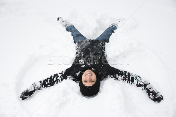 Woman making snow angel. Stock photo © iofoto