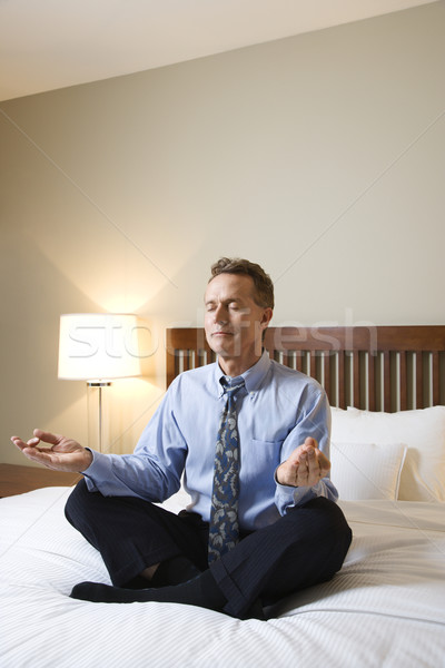 Businessman Meditating on Bed Stock photo © iofoto