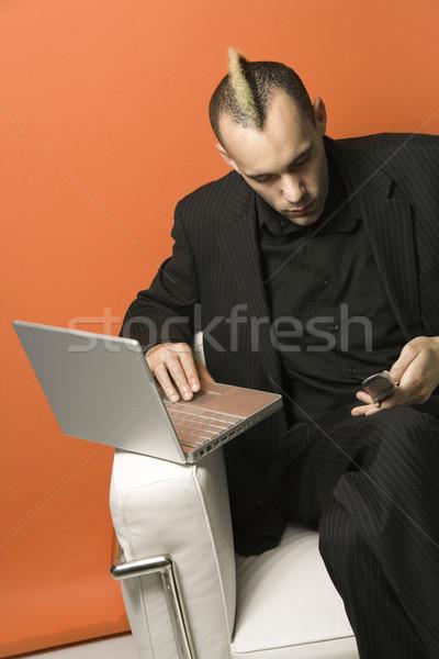 Businessman on laptop and cellphone. Stock photo © iofoto