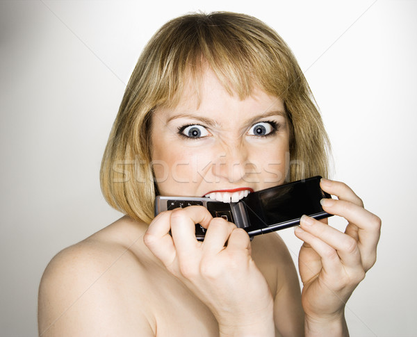Woman biting phone. Stock photo © iofoto