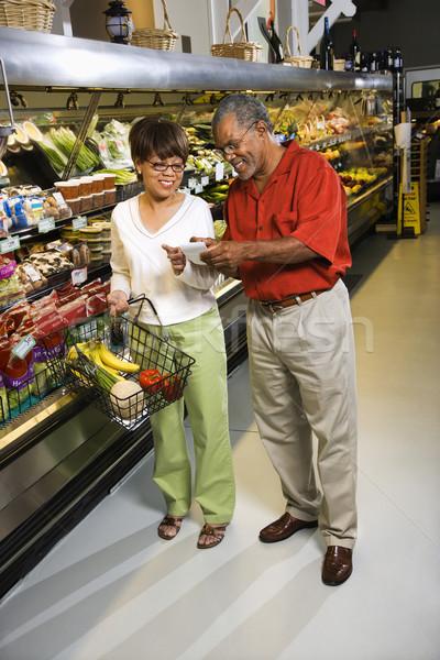 Para supermarket w średnim wieku sklep spożywczy wskazując Zdjęcia stock © iofoto