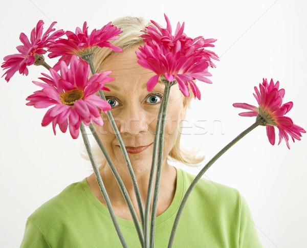 Woman looking through flowers. Stock photo © iofoto