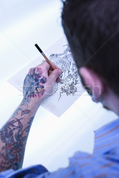 Tattoo artist drawing. Stock photo © iofoto